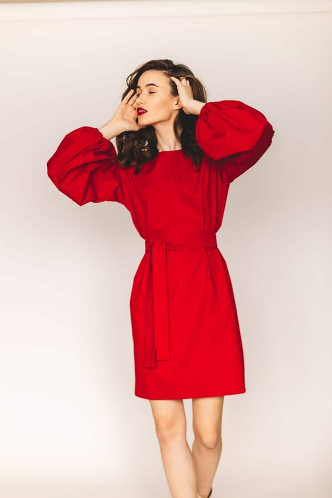 A woman wearing a lovely red dress that has lantern sleeves.