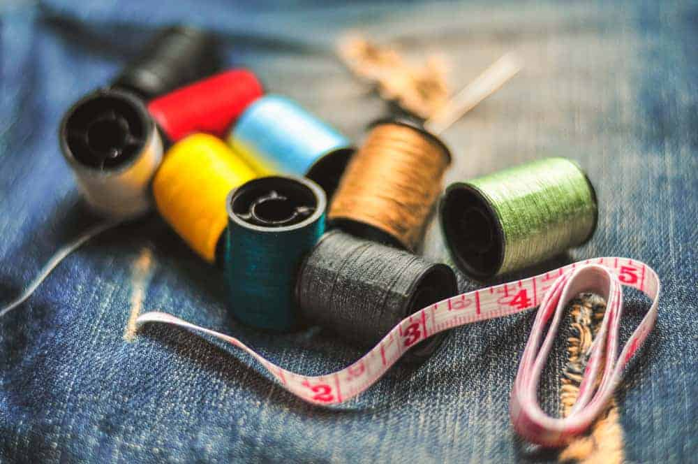 Various sewing essentials on a denim fabric.