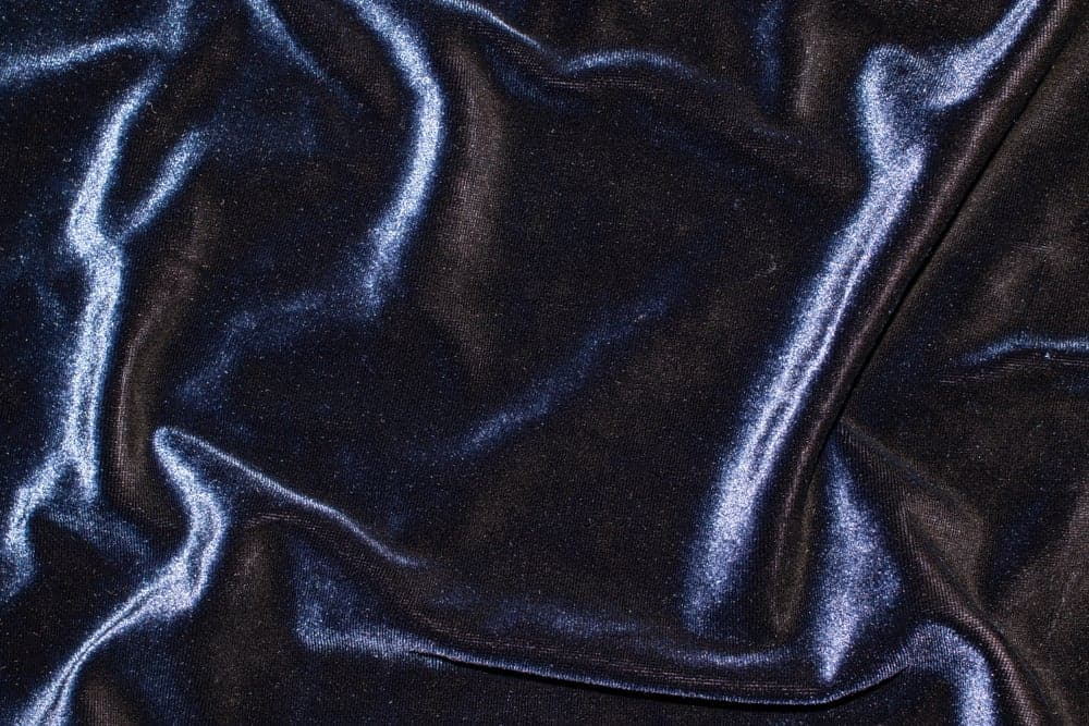 This is a close look at a navy blue stretch velvet fabric.
