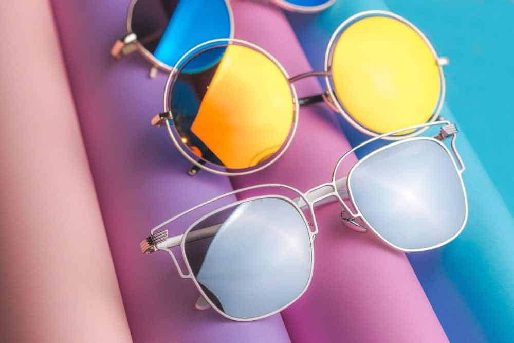 A close look at various pairs of sunglasses on a colorful surface.