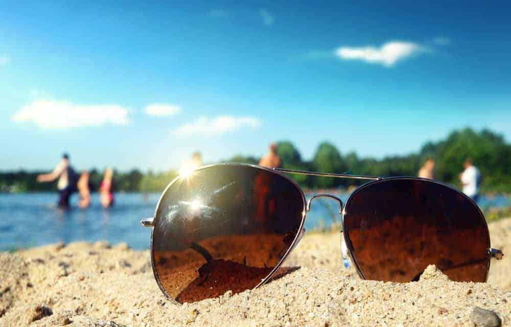 A pair of fashionable sunglasses with tinted lenses on the beach sand.