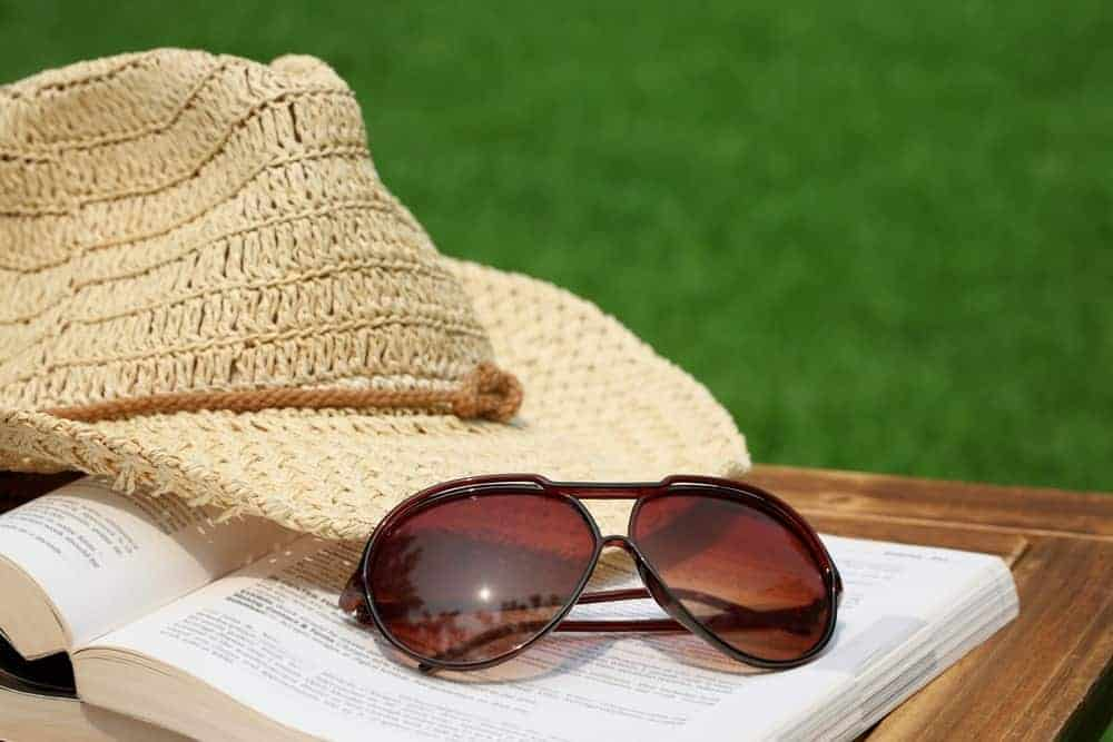 A pair of brown reading sunglasses with a book and a hat outdoors.