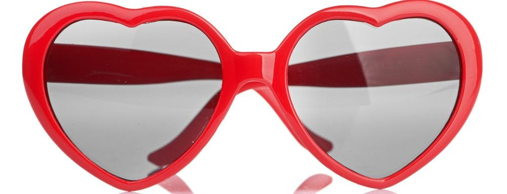 This is a close look at a pair of red heart-shaped sunglasses.
