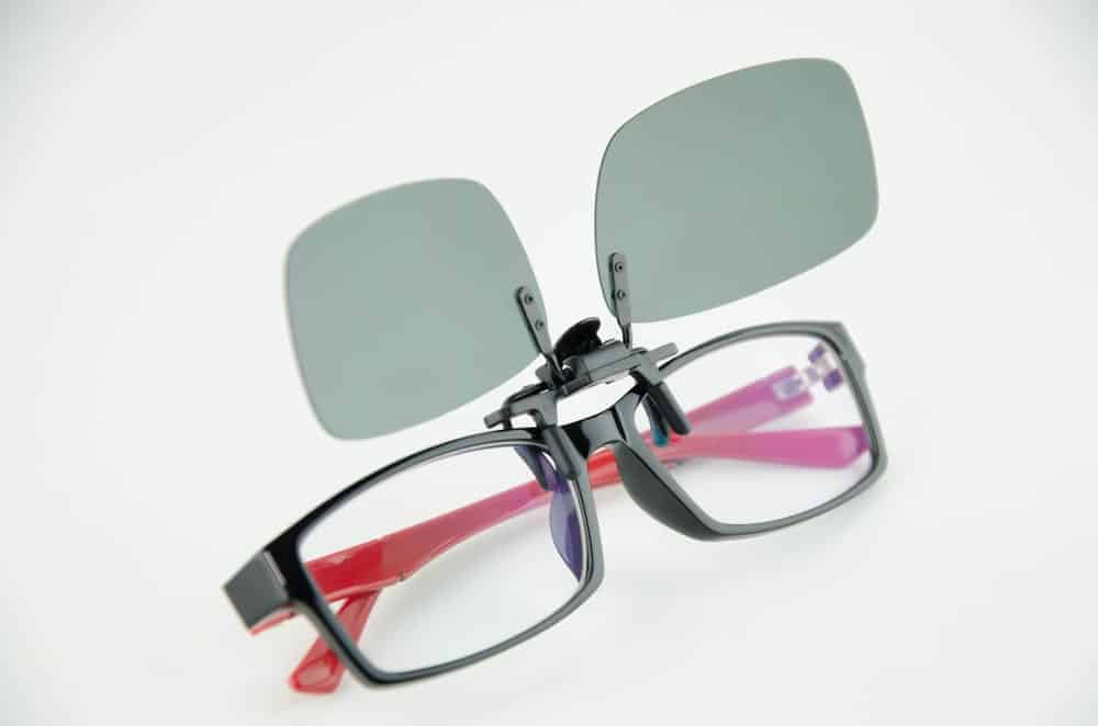 A pair of clip-on black sunglasses on a pair of reading glasses.