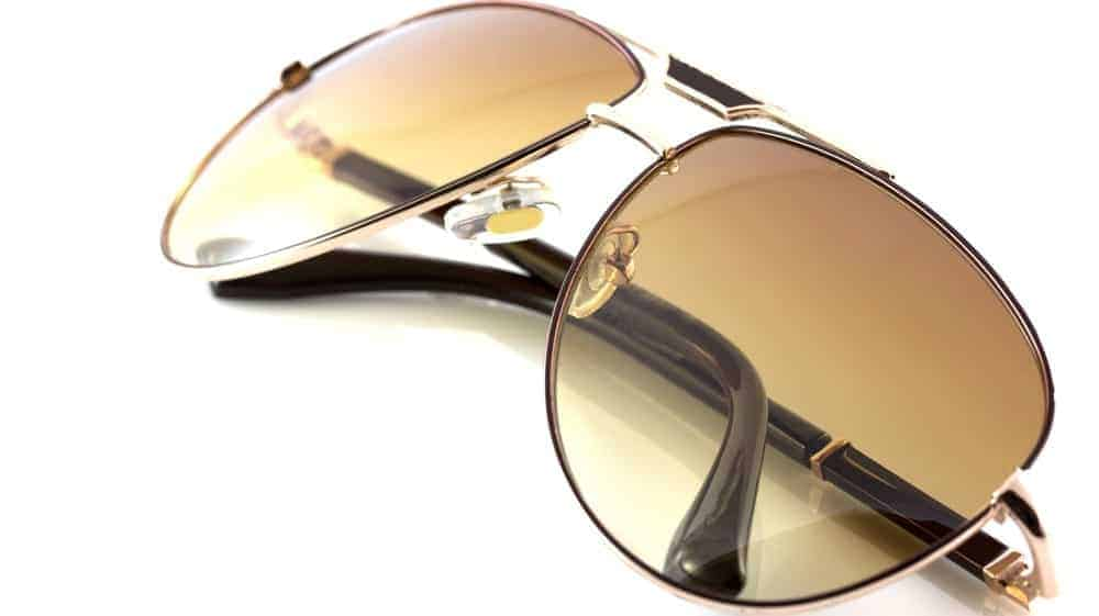 A close look at a pair of sunglasses with metal frames and tinted lenses.