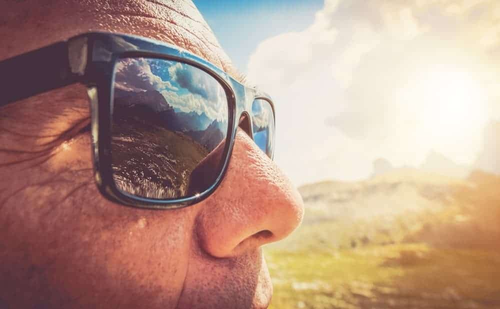 A close look at a man wearing a pair of sunglasses that protects his eyes from UV rays.