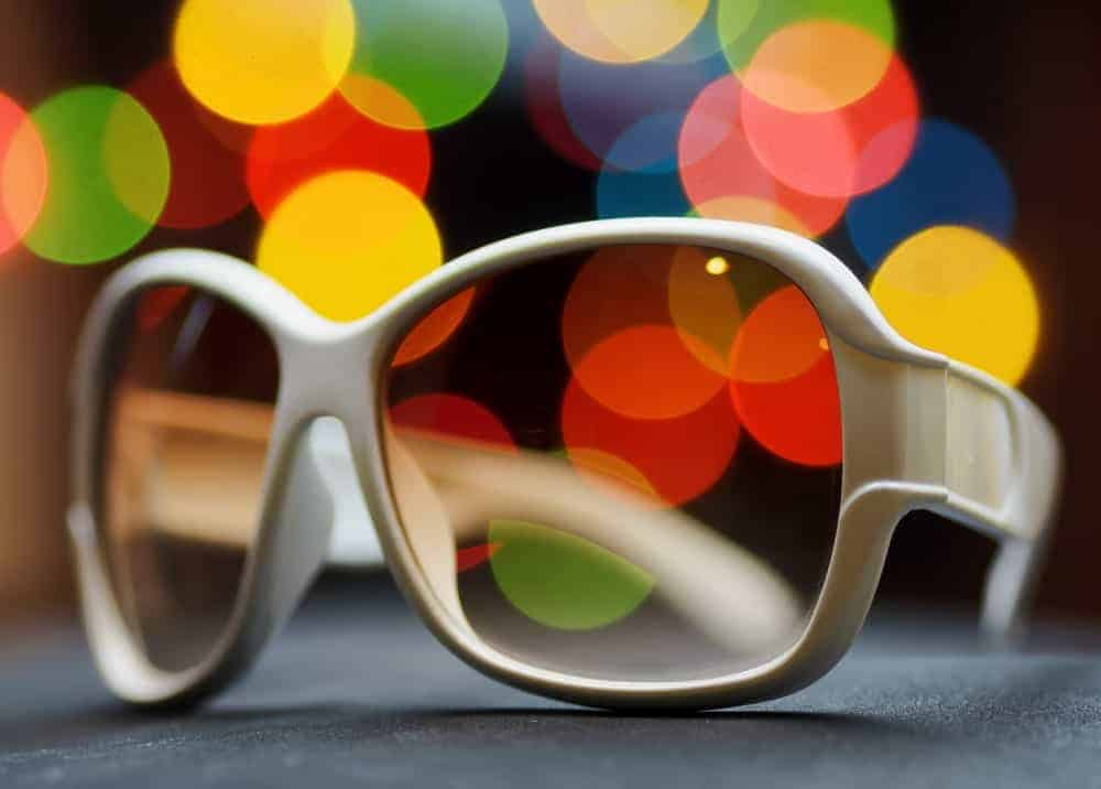 This is a close look at a pair of white sunglasses with plastic lenses.
