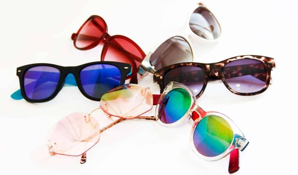 This is a close look at a bunch of various sunglasses with colored lenses.