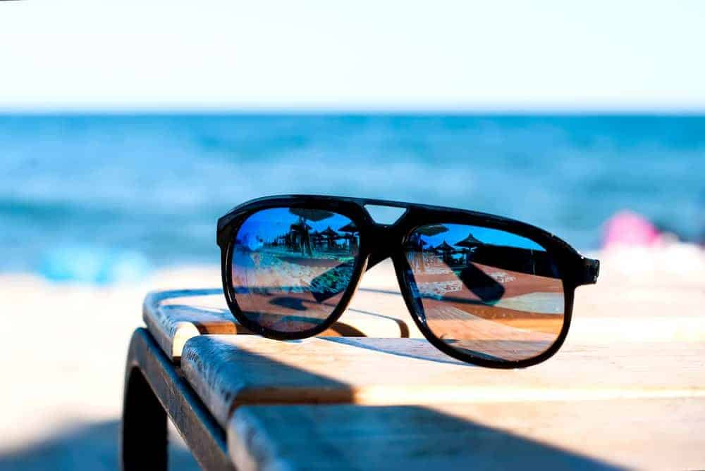 A pair of mirrored sunglasses on a wooden bench at the beach.