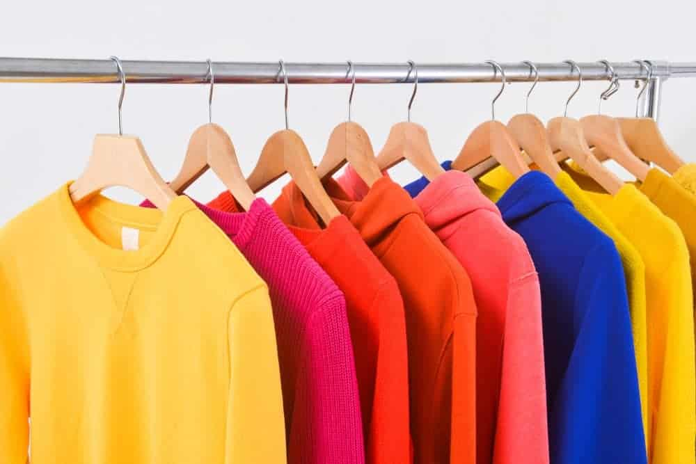 A close look at a rack of various colorful sweatshirts.
