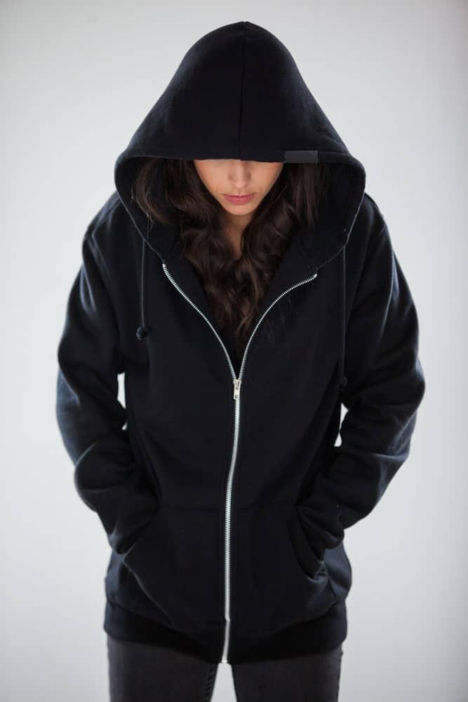 A woman wearing a zippered sweatshirt with hood.