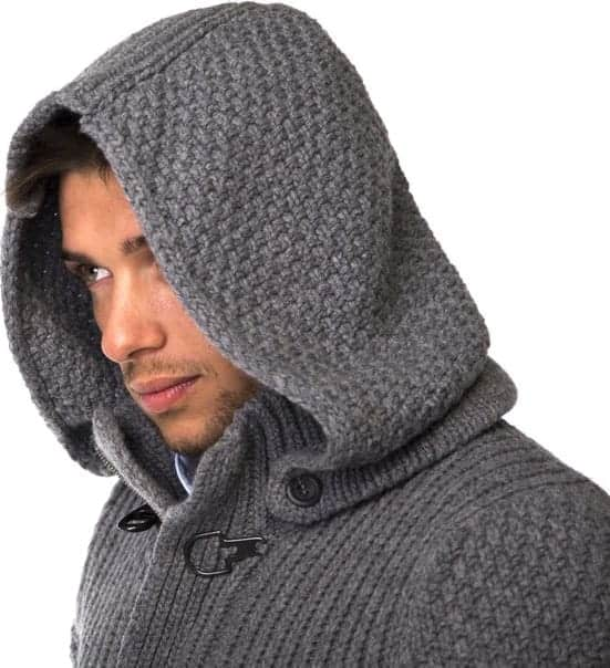 A close look at a man wearing a gray knitted sweatshirt with hood attachment.