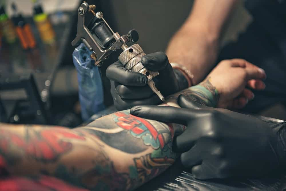 This is a close look at a man having his left arm tattooed.