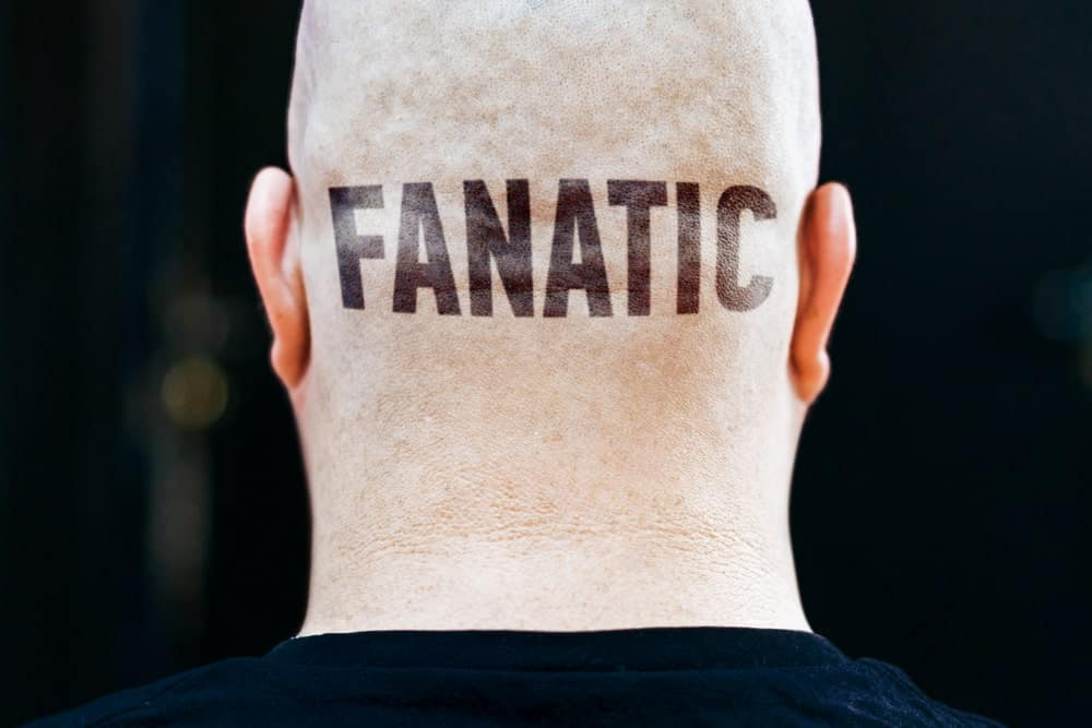 This is a close look at the back of a man's head with the word FANATIC tattooed on it.