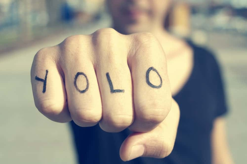 This is a close look at a man's fist with the letters YOLO tattooed on it.
