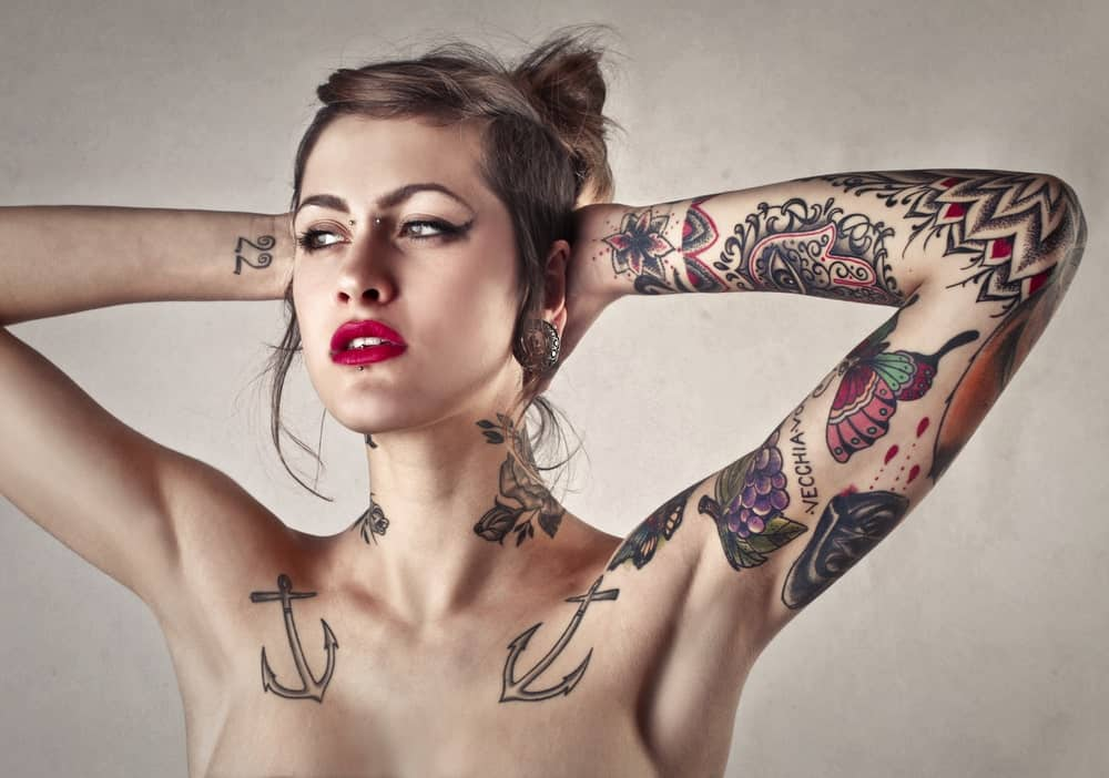 A woman with multiple tattoos on her arms and neck.