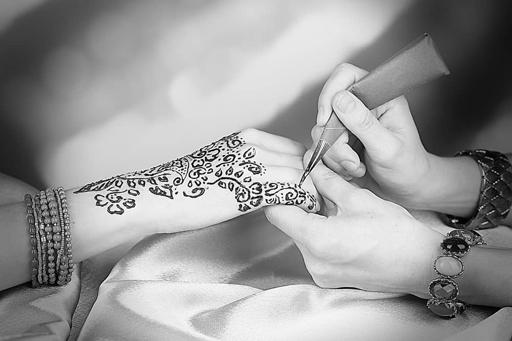 This is a close look at a woman's hand being tattooed with floral patterns.