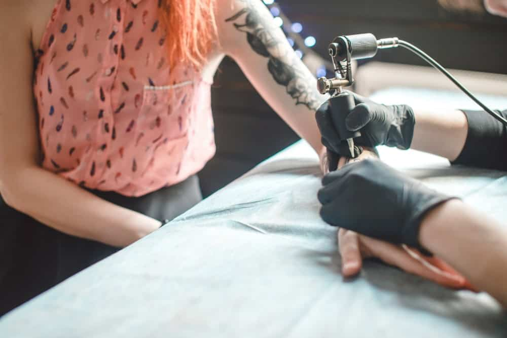 This is a close look at a woman having her left arm tattooed.
