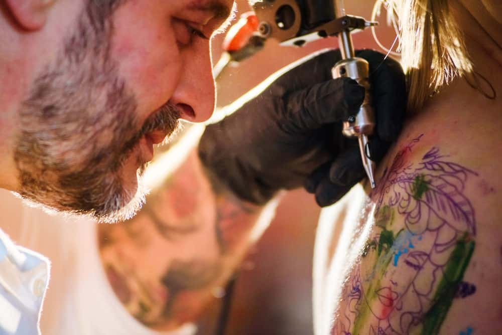 This is a close look at a woman having her back tattooed.