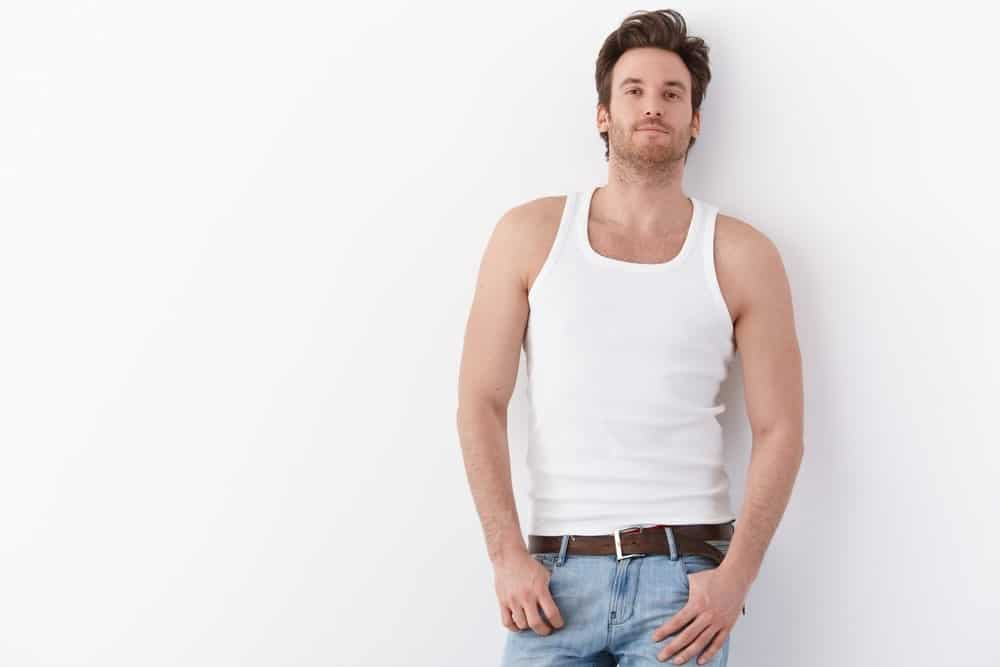 This is a man wearing a white tank top undershirt with his jeans.