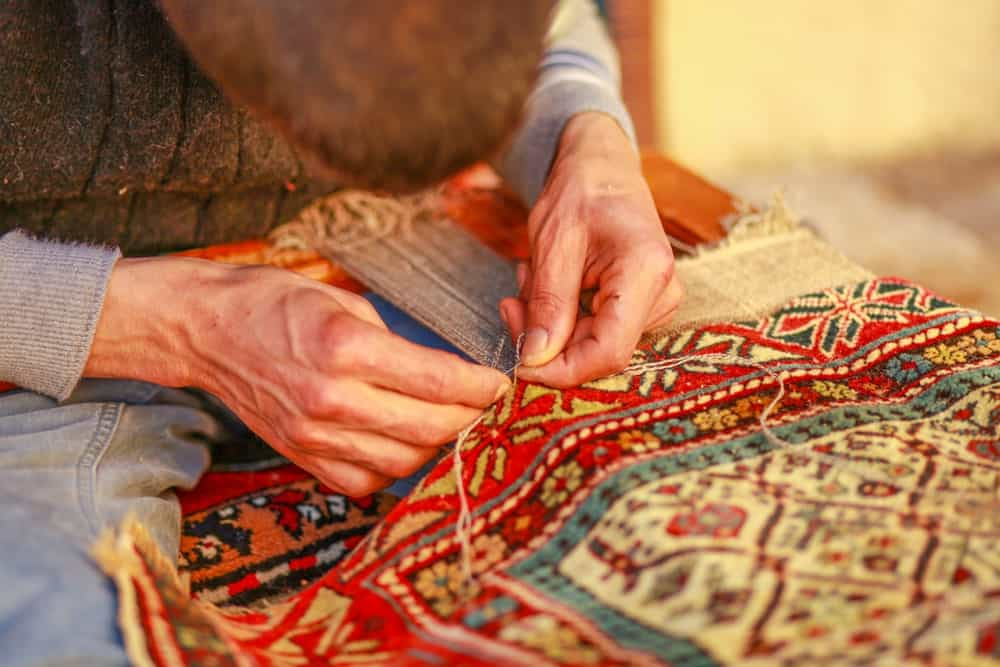 This is a close look at a man weaving a carpet.