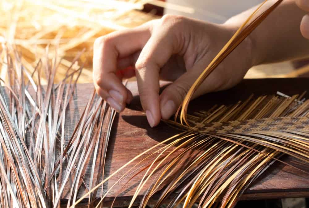 This is a close look at a pair of hands weaving a basket.