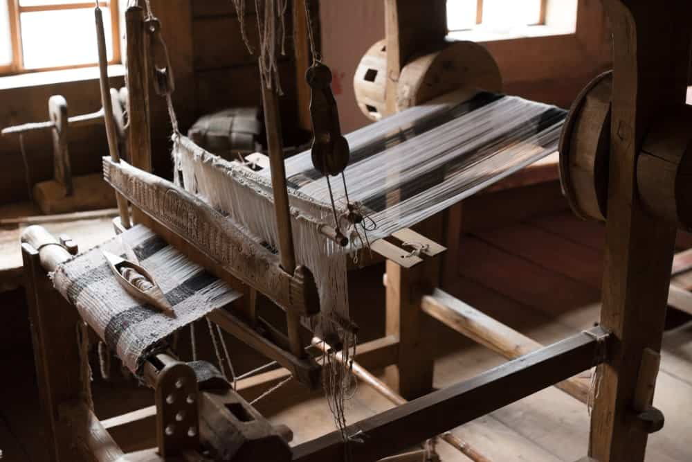 This is a close look at an old wooden loom within a wooden cabin.