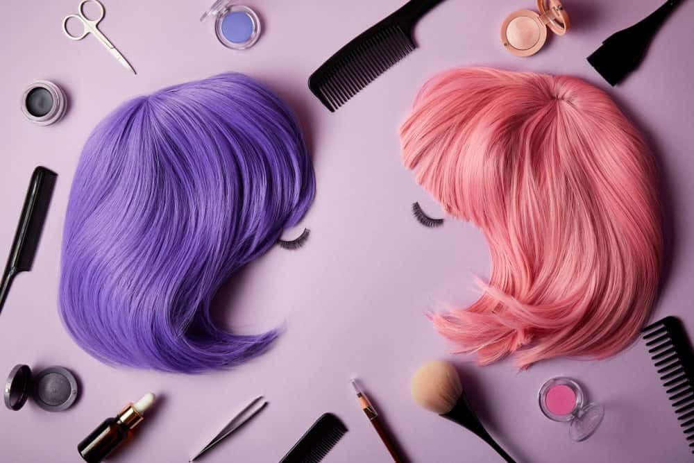 A pair of colorful wigs surrounded by accessories and beauty essentials.