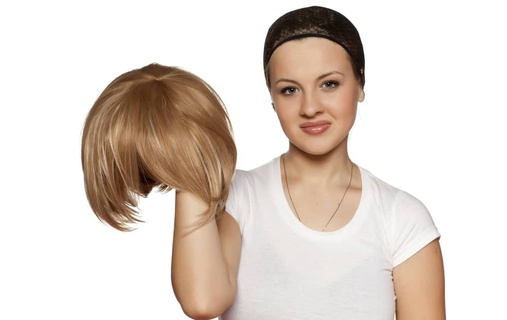 A woman wearing a wig cap holding a wig.