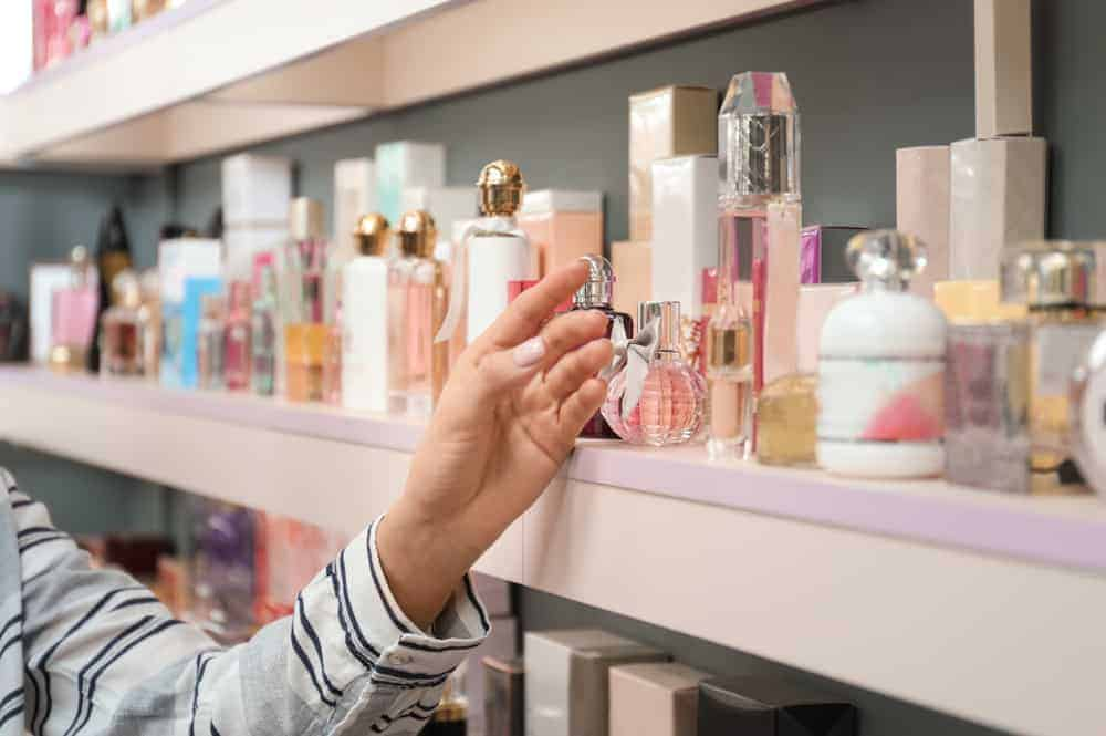 Woman picking out a perfume on a display shelf.