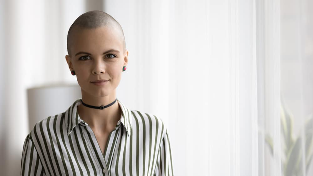 Woman with shaved hair wearing a striped polo blouse.