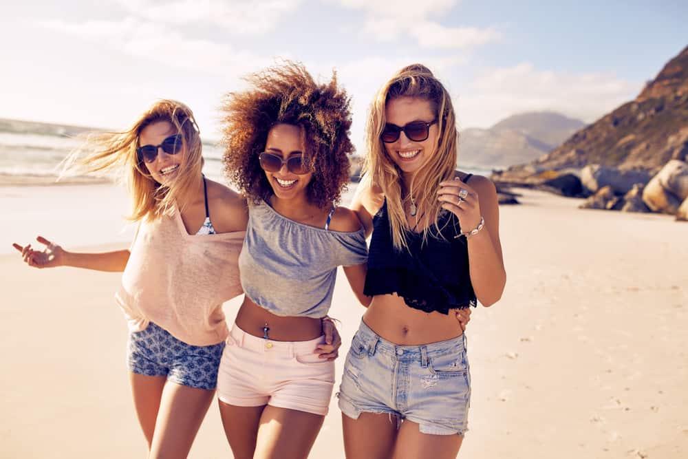 Three female friends walking along the sea shore.