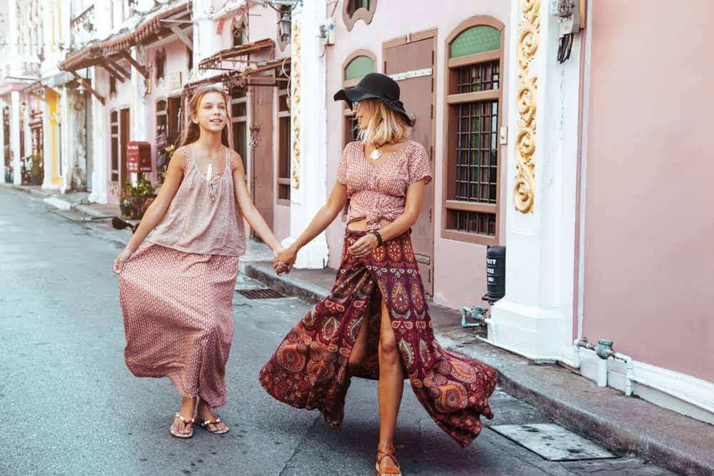 Mom and daughter in bohemian dress walking down the street.
