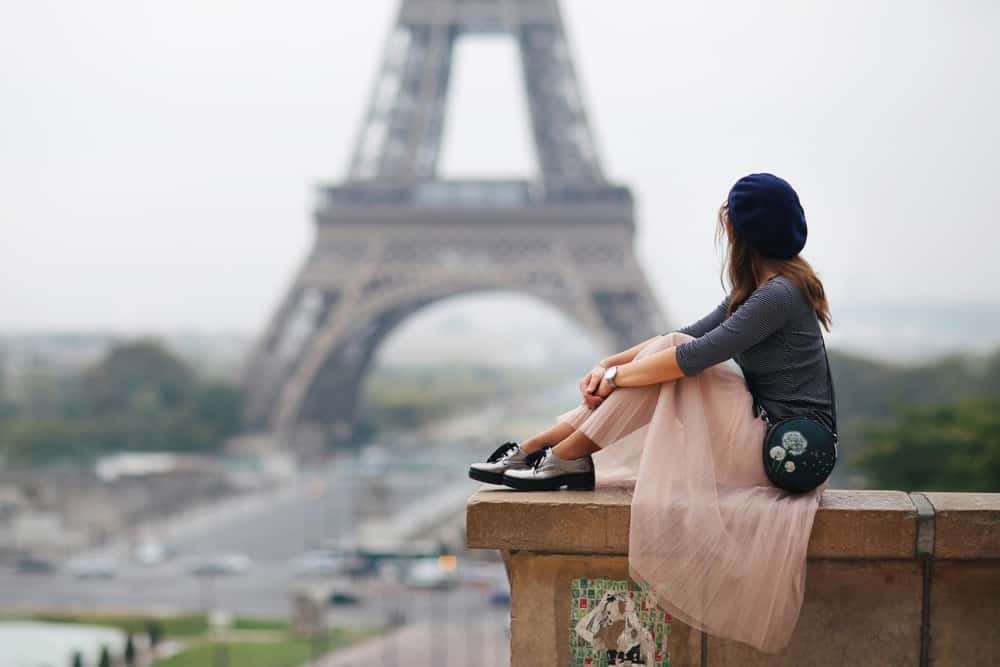 Woman in sheer skirt staring at the eiffel tower.
