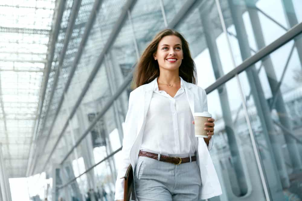 Woman in a business casual attire holding a cup of coffee on her way to work.