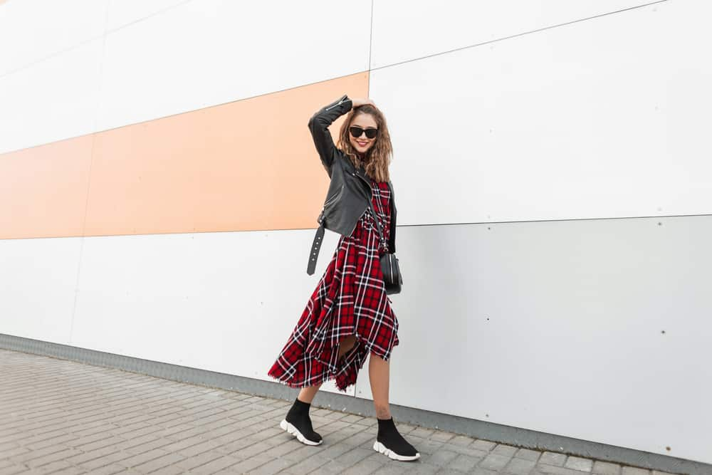 Woman in a red checkered casual dress, sunglasses, and a crossbody bag walking on the street.