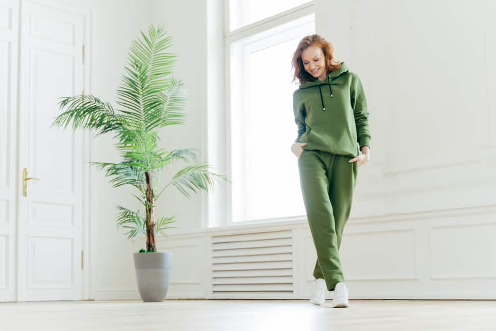 Woman in a matching green tracksuit exercising indoors.