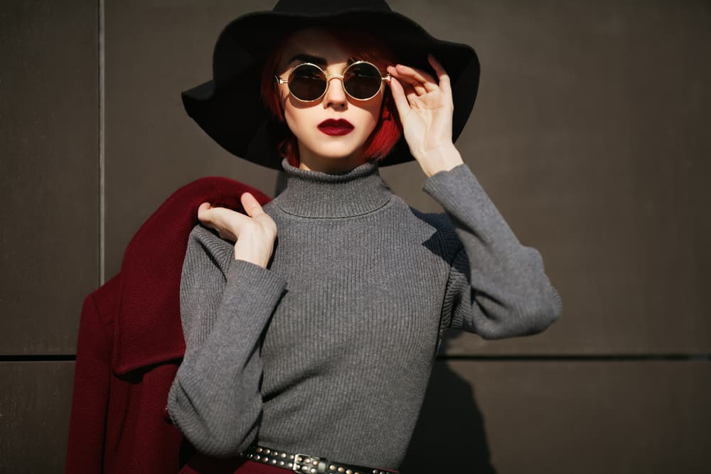 Female model wearing stylish wide-brimmed hat, sunglasses, and a turtleneck top.