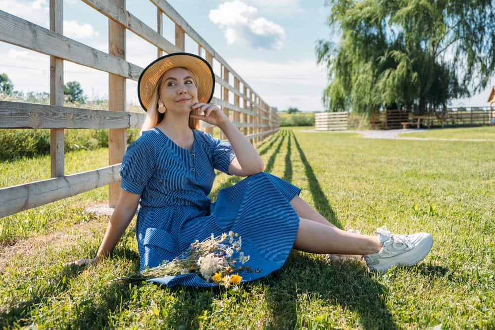 Woman in a straw hat, blue dress and sneakers sitting on a lawn near the fence.