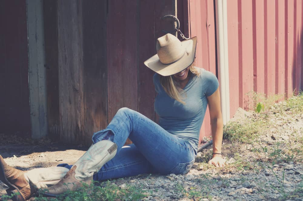 Cowgirl sitting outside a rustic barn.