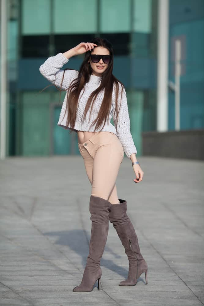 Woman wearing knitted sweater, knee-high boots and sunglasses.