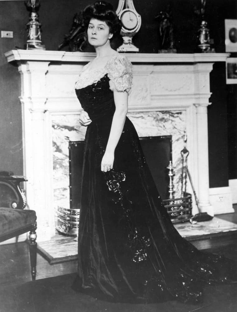 Woman in a gibson girl outfit standing near a fireplace.