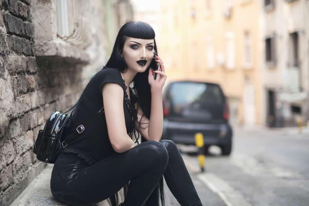 Goth girl sitting near the street.