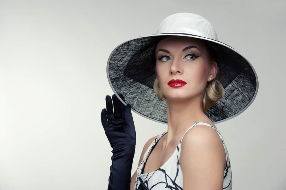A portrait of a woman wearing a white hat that matches her dress.