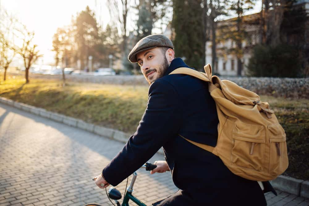 A man on a bike wearing a backpack and a brixton hat.