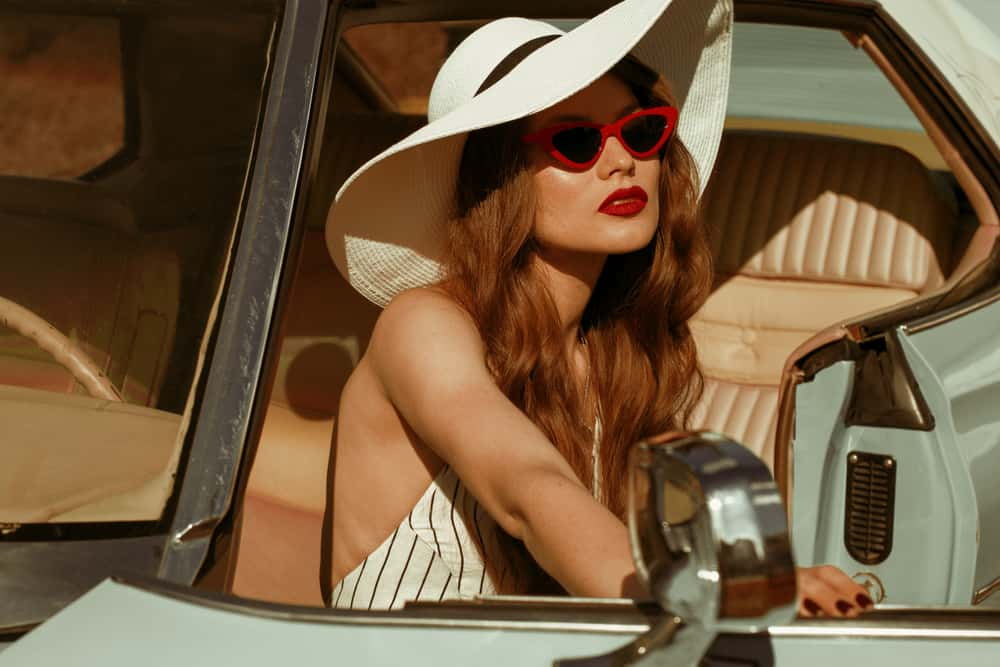 A woman wearing a wide brim hat and sunglasses in a vintage car.