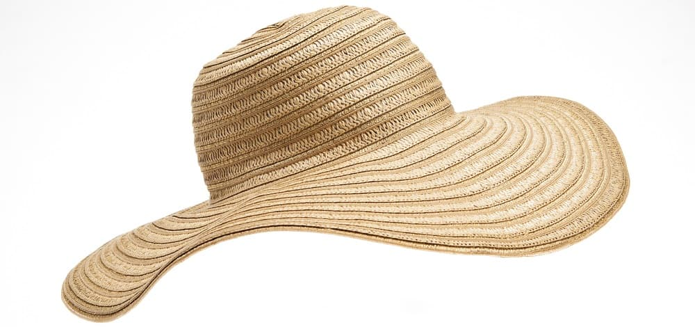 This is a close look at a woman's wide brim straw beach hat.