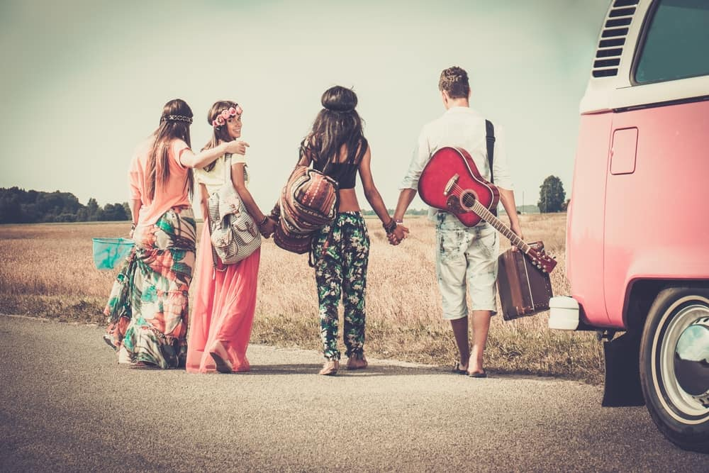Hippie friends with luggage and guitar.