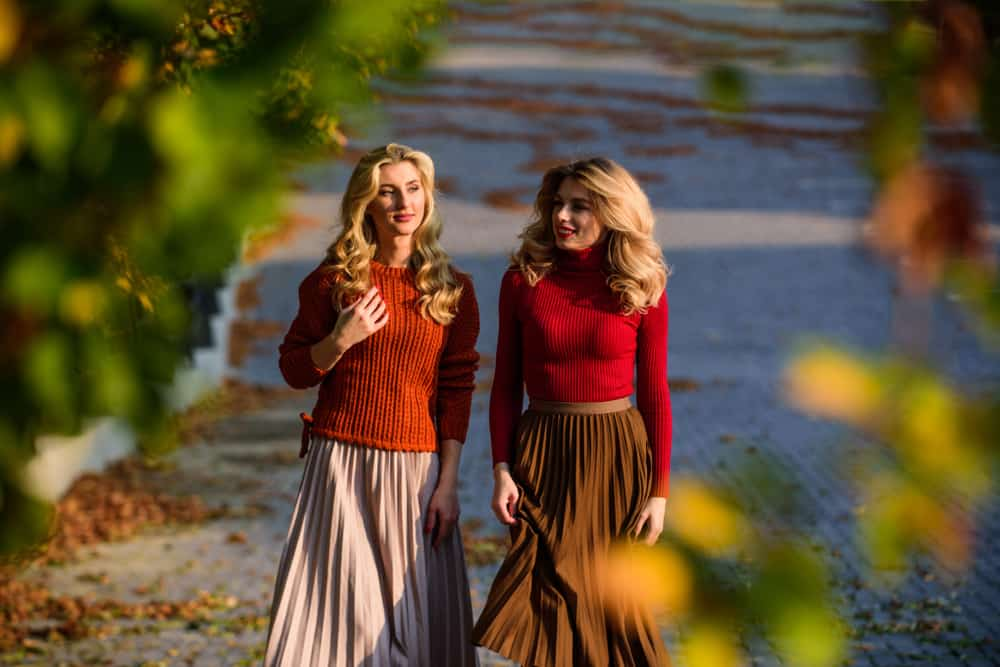 Two women in preppy clothes walking on the street during autumn.