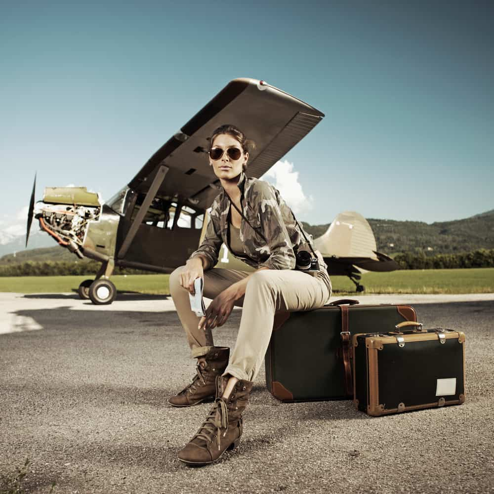 Woman in military inspired outfit sitting on a suitcase against an airplane backdrop.
